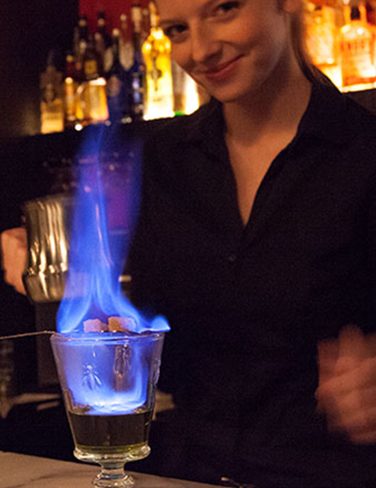 Bartender a making flaming drink